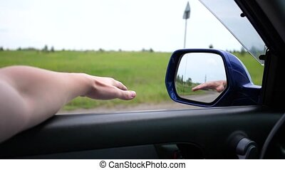 The movement of the car on the highway. The driver drives with the window open. Reflection hands in the mirror. family trip