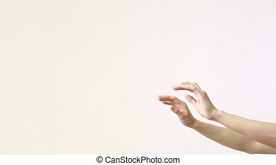 The moving hands of an orchestra conductor directing the musicians. Close-up shot. White background