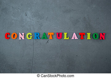 The multicolored congratulation word is made of wooden letters on a grey plastered wall background.