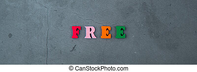 The multicolored free word is made of wooden letters on a grey plastered wall background.