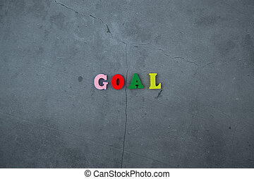 The multicolored goal word is made of wooden letters on a grey plastered wall background.