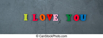 The multicolored I love you word is made of wooden letters on a grey plastered wall background.