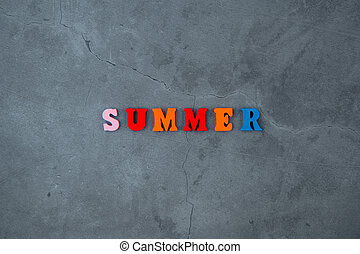 The multicolored summer word is made of wooden letters on a grey plastered wall background.