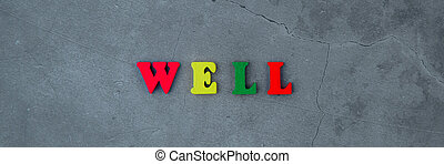 The multicolored well word is made of wooden letters on a grey plastered wall background.