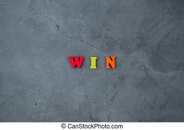 The multicolored win word is made of wooden letters on a grey plastered wall background.