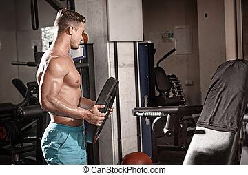 Muscular bodybuilder guy doing exercises with weight in gym