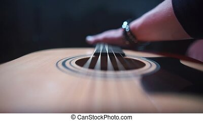 The musician finger touches the strings of an acoustic guitar