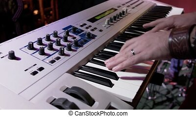 The musician plays a synthesizer in a nightclub under colored spotlights. A male keyboard player performs at a party.