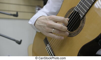 The musician plays the classical guitar. Close up of right hand