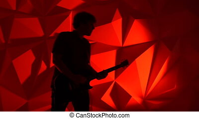 The musician plays the guitar. Guitarist silhouette on red background. Background photography in a photo studio