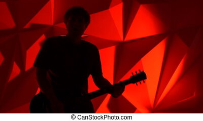 The musician plays the guitar. Rock guitarist silhouette on red background