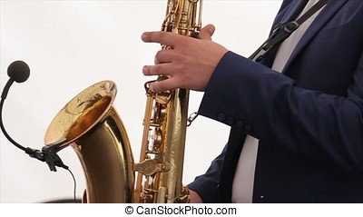 the musician plays the saxophone. Happy saxophonist plays music on sax in elegant suit on white background. Hands of groom play on saxophone. Saxophone Player at Holiday Time. Saxophonist. Man playing on saxophone against the background of wedding or banket. Party