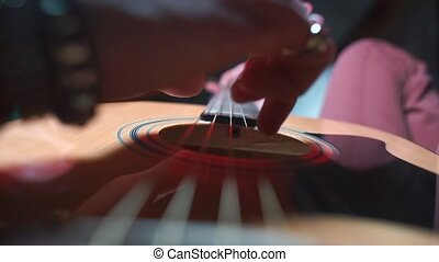 The musician plays the strings of a guitar at a concert.