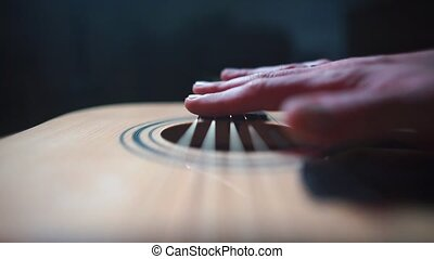 The musician plays with his fingers on the strings of a guitar.