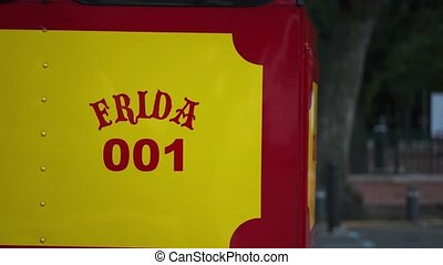 4k Video of the name Frida and number 001 on a red and yellow trolley car with trees in the background