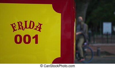 4k Video of the name Frida and number 001 on a red and yellow trolley car with trees, people, and cars as background