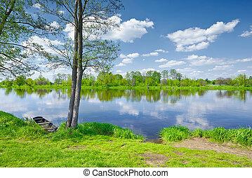 The Narew River Scenery. Old boat on riverbank.