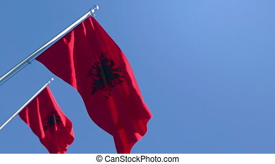The national flag of Albania is flying in the wind against a blue sky