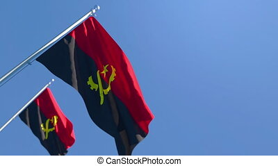 The national flag of Angola is flying in the wind against a blue sky