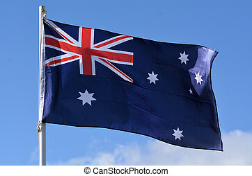 The National flag of Australia against blue sky.