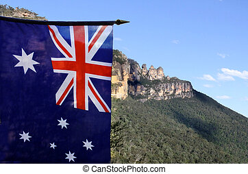 The National flag of Australia flay beside the Three Sisters Blue Mountains of New South Wales Australia