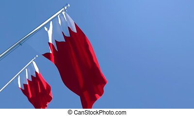 The national flag of Bahrain is flying in the wind against a blue sky