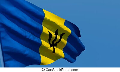 The national flag of Barbados is flying in the wind.