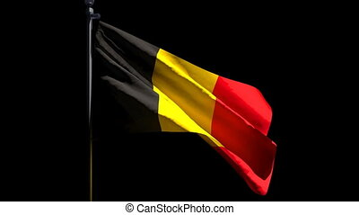 The national flag of Belgium is flying in the wind against a black background.