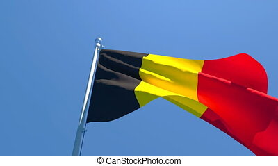 The national flag of Belgium is flying in the wind against a blue sky.