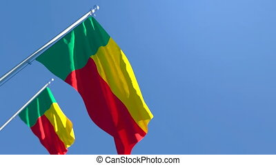 The national flag of Benin is flying in the wind against a blue sky
