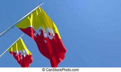 The national flag of Bhutan is flying in the wind against a blue sky