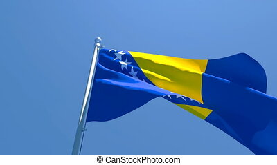 The national flag of Bosnia and Herzegovina is flying in the wind against a blue sky.