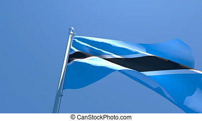The national flag of Botswana is flying in the wind against a blue sky.