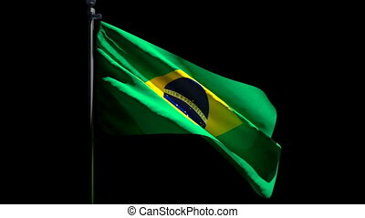 The national flag of Brazil is flying in the wind against a black background