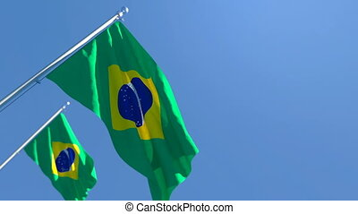 The national flag of Brazil is flying in the wind against a blue sky
