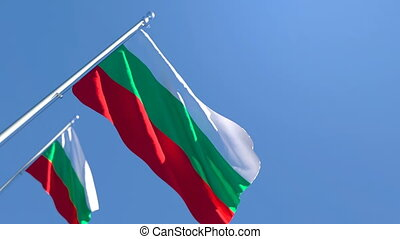 The national flag of Bulgaria is flying in the wind against a blue sky
