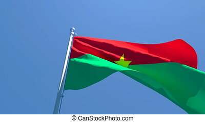 The national flag of Burkina Faso is flying in the wind against a blue sky