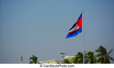 The national flag of Cambodia flying in the sky background