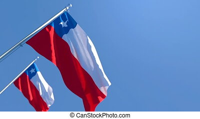 The national flag of Chile is flying in the wind against a blue sky
