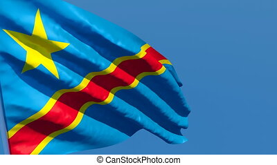 The national flag of Congo flutters in the wind against a blue sky.