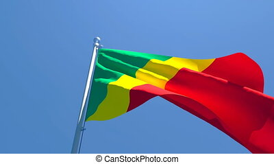 The national flag of Congo is flying in the wind against a blue sky.