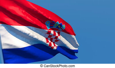 The national flag of Croatia flutters in the wind against a blue sky