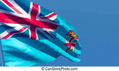 The national flag of Fiji flutters in the wind against a blue sky