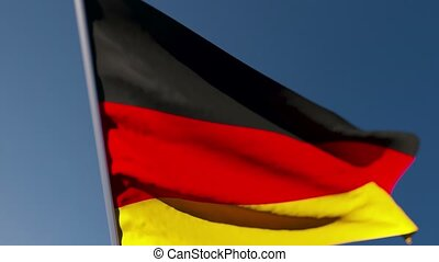 The national flag of Germany flutters in the wind against a blue sky