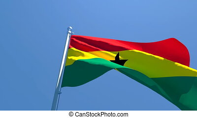 The national flag of Ghana is flying in the wind against a blue sky.