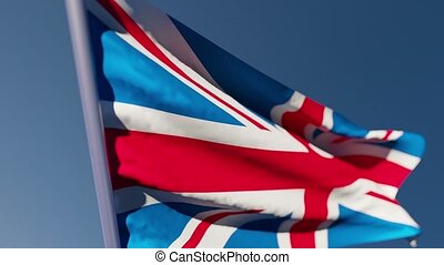 The national flag of great Britain flutters in the wind against a blue sky