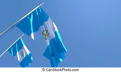 The national flag of Guatemala is flying in the wind against a blue sky.