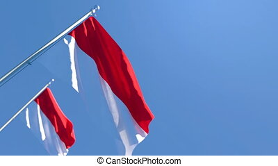 The national flag of Indonesia is flying in the wind against a blue sky