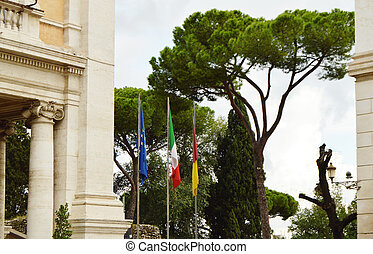The national flag of Italy, the European Union EU flag of the city of Rome on the flagpole near the city Hall of Rome, on 7 October 2018