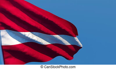 The national flag of Latvia is flying in the wind